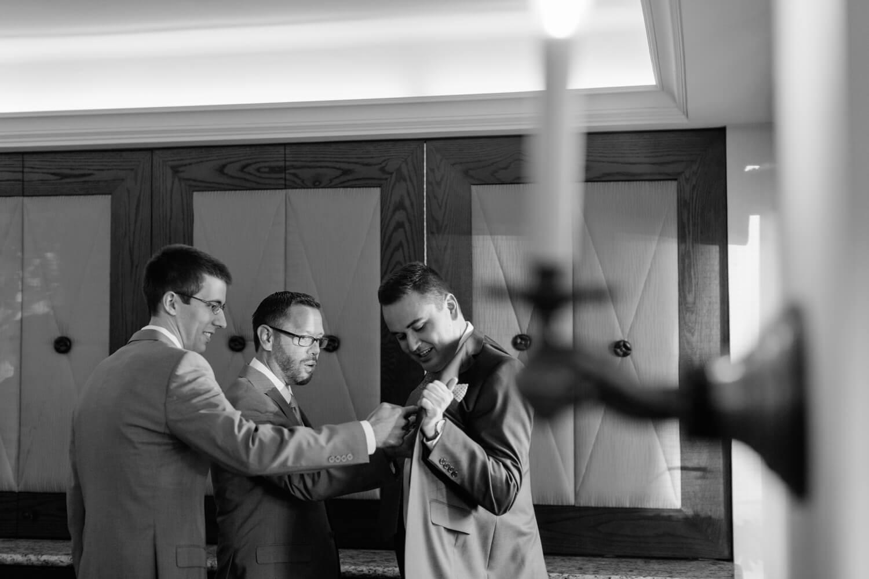 groomsmen help groom with jacket before all hallows wedding