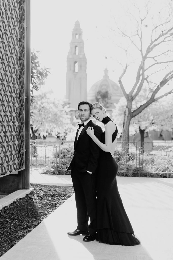 couple pose near mingei museum with california tower in background balboa park