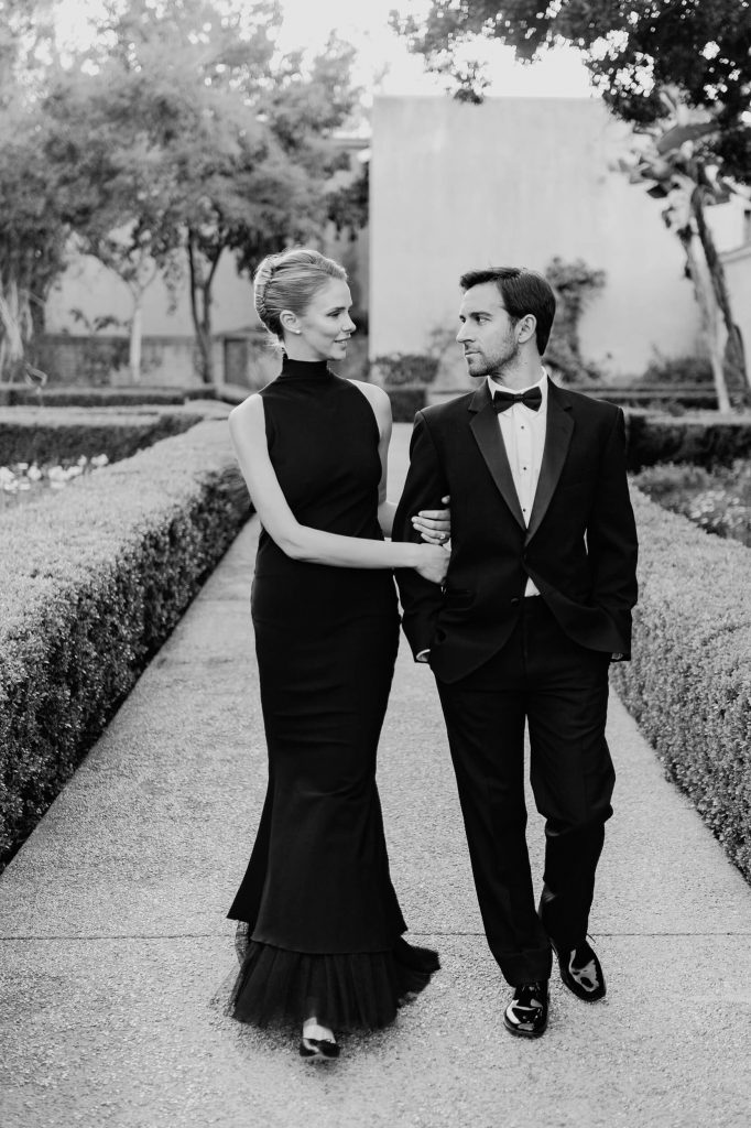 woman in long black gown walks with fiancee in tuxedo through alcazar gardens classic engagement photo