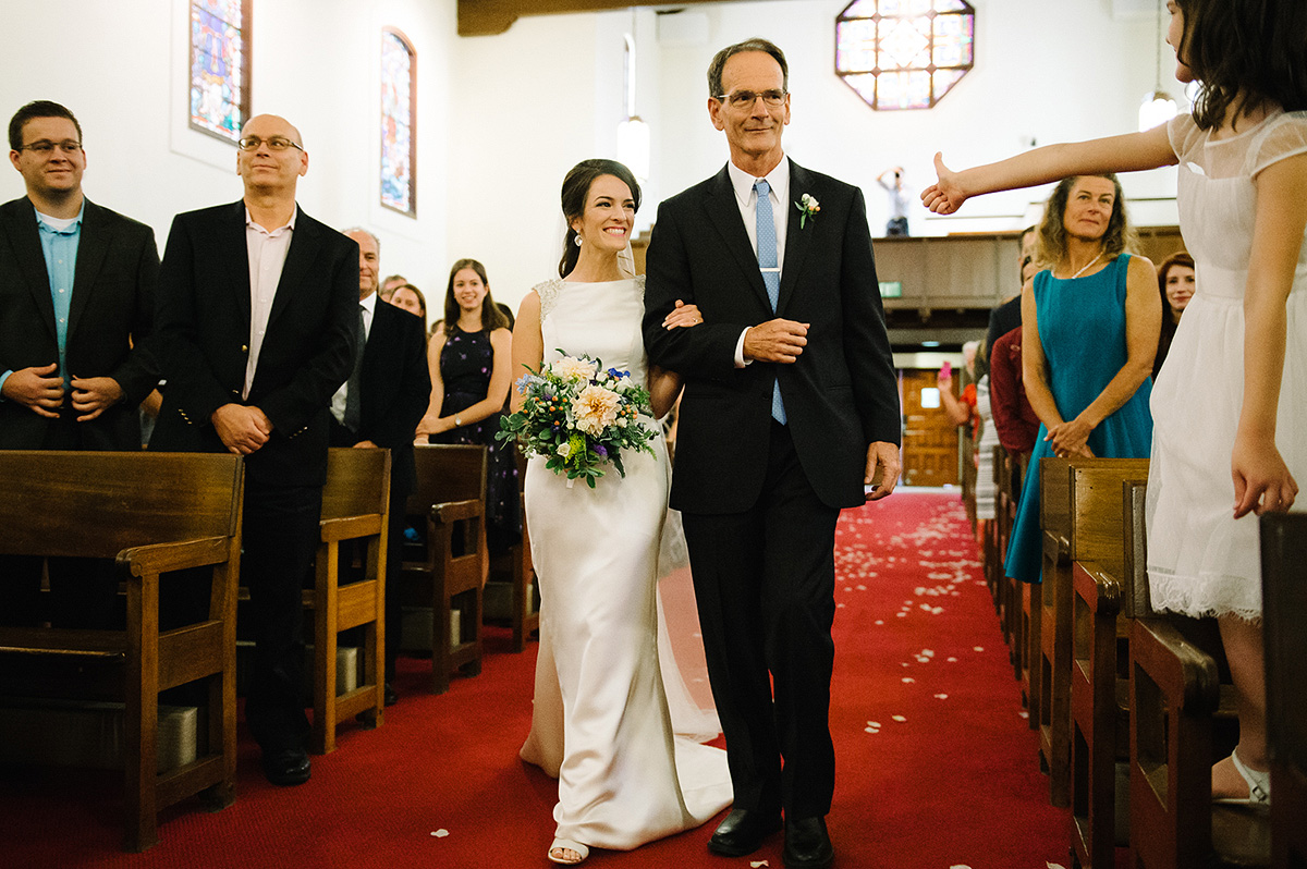 flower girl gives thumbs up to bride with father processional north chapel