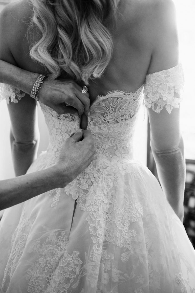 hands fasten clasp on monique lhuillier wedding gown