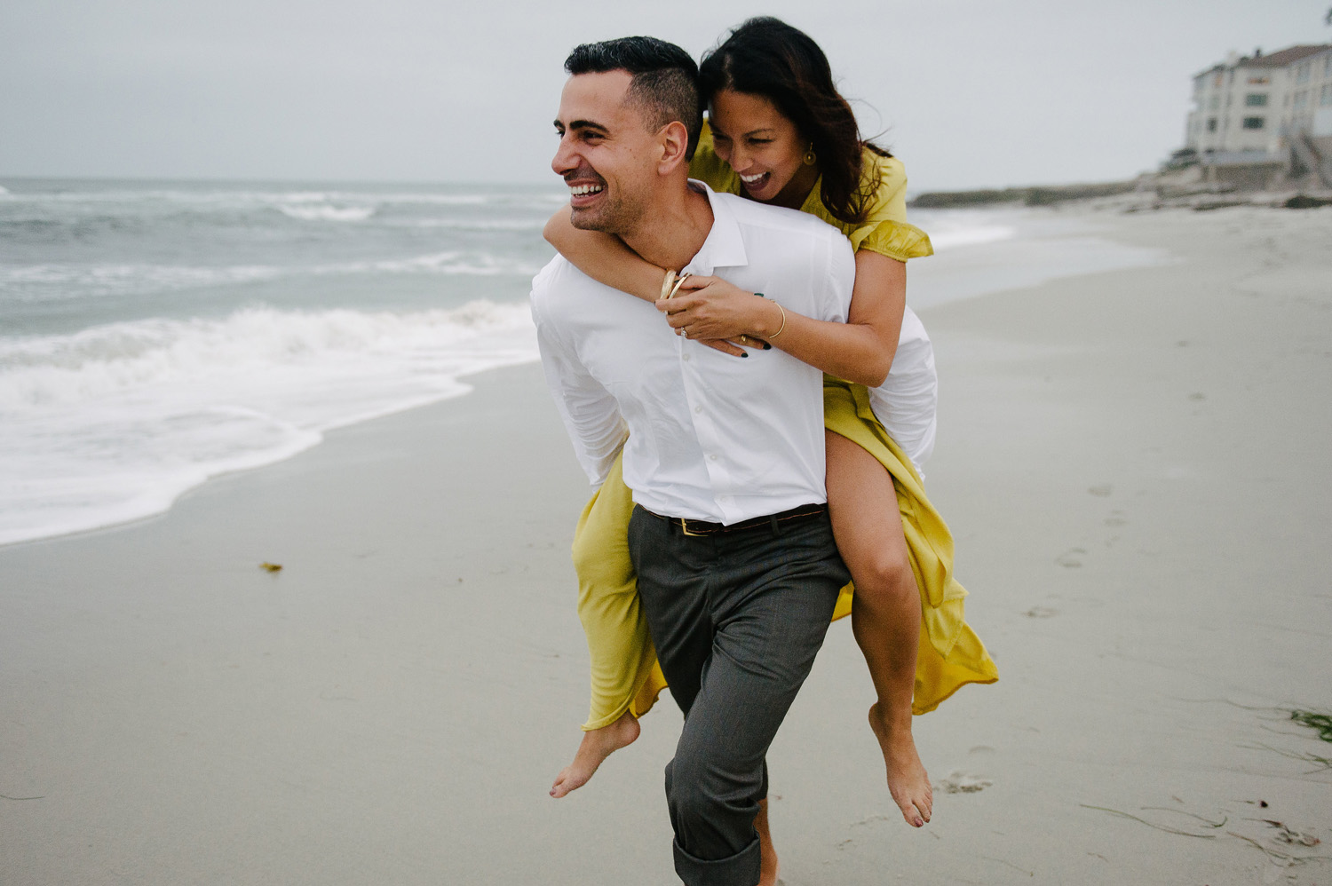 man carries fiancee on back on sand at marine street beach in la jolla