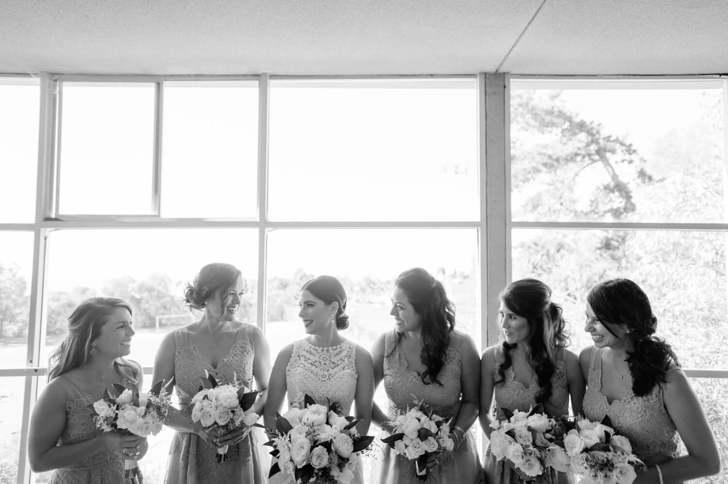 bride and bridesmaids pose with bouquets near window before all hallows wedding