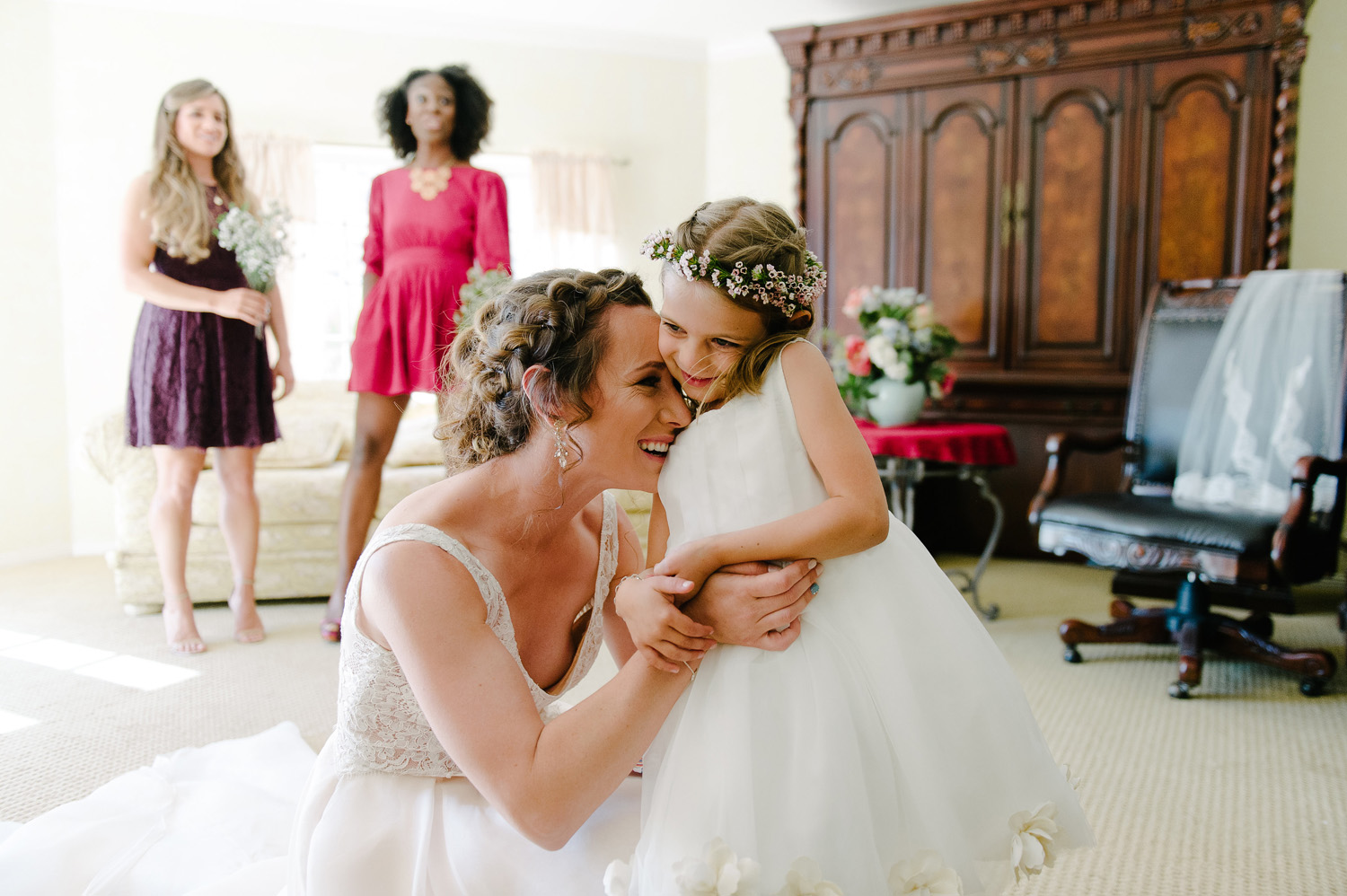 bride laughs hugs flower girl