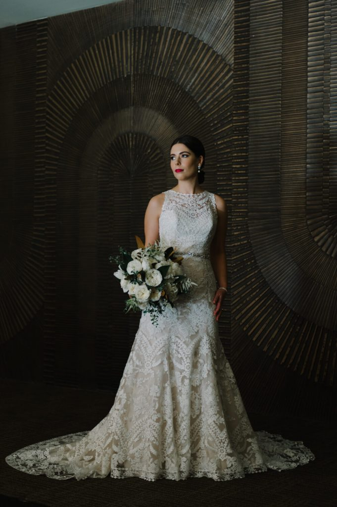 bride lace gown pose textured wall all hallows church la jolla wedding