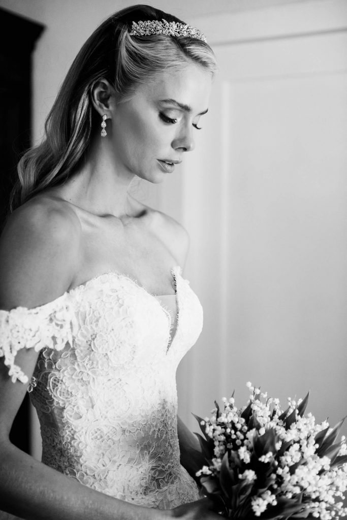 bride in tiara wearing monique lhuillier wedding gown with lily of the valley bouquet