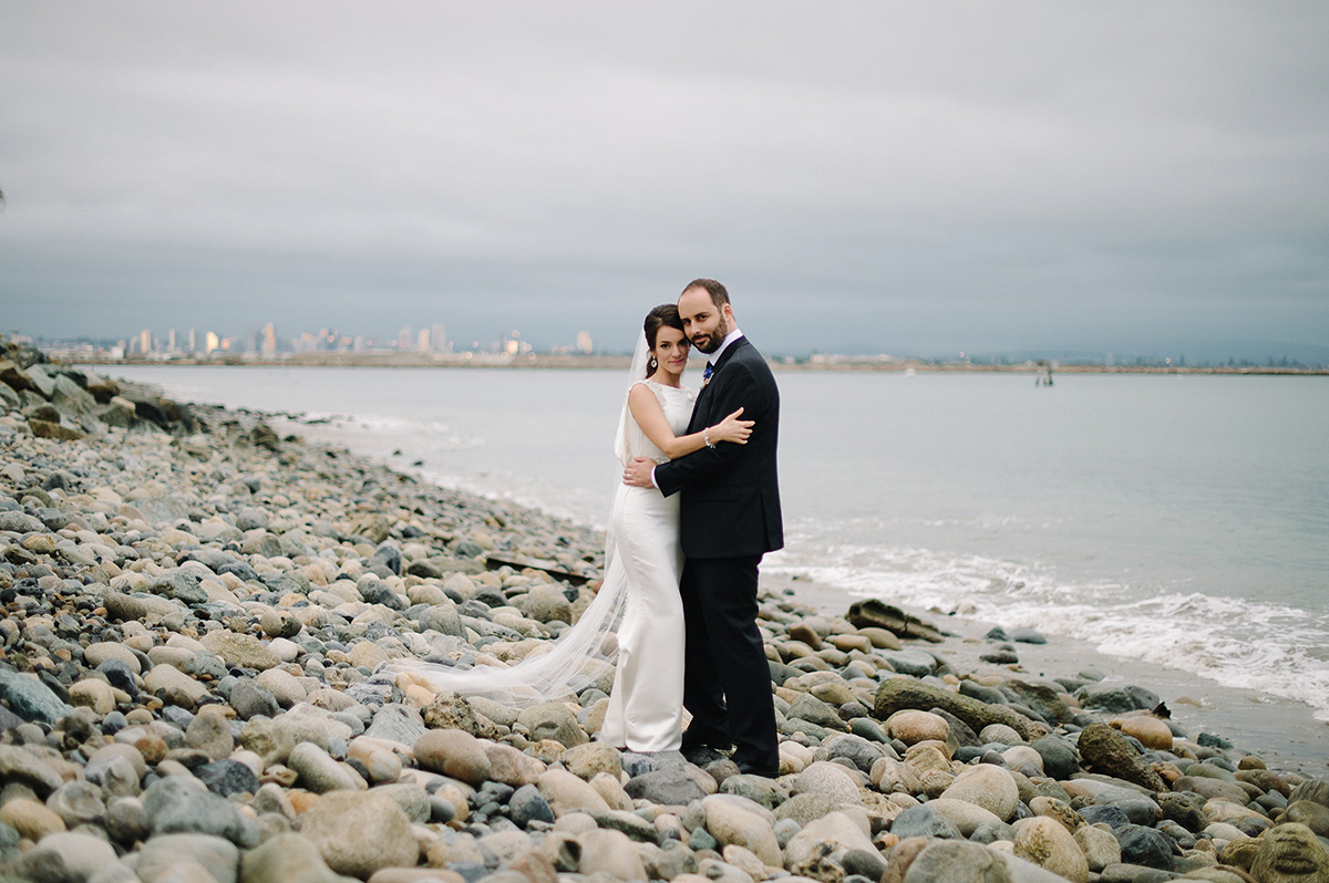 bride groom pose rocks with san diego skyline in background