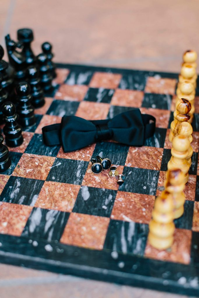 groom's bowtie and cufflinks on marble chessboard
