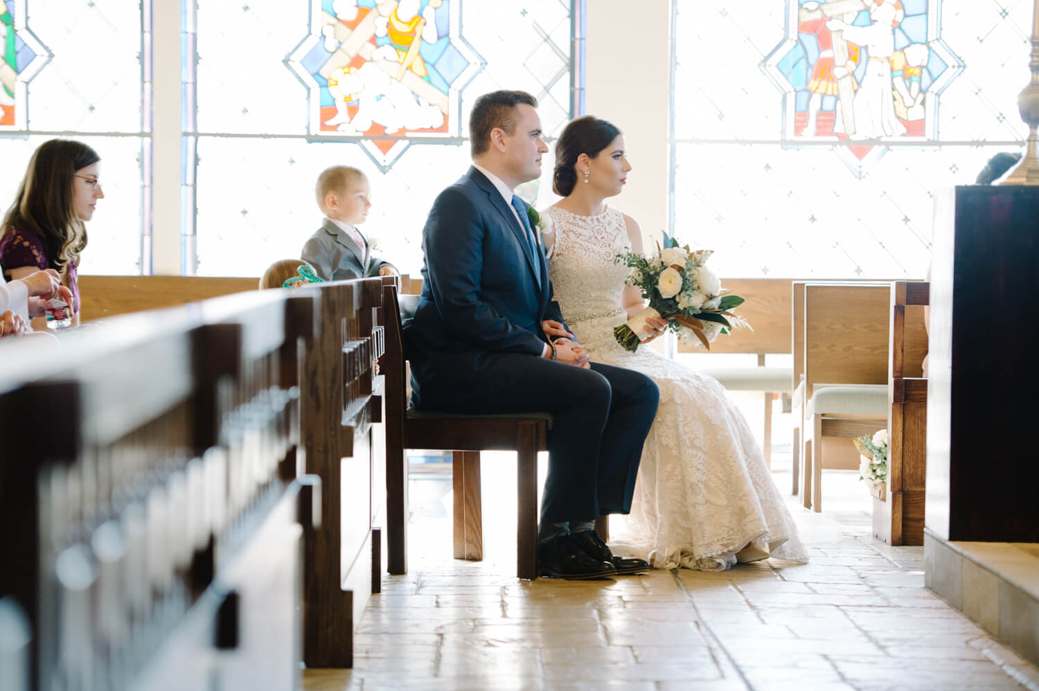 bride and groom sit during all hallows wedding ceremony