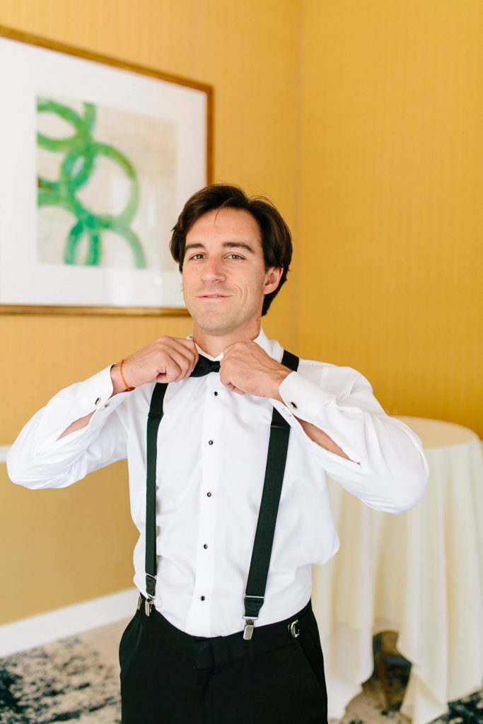 groom in white shirt and suspenders puts on bowtie