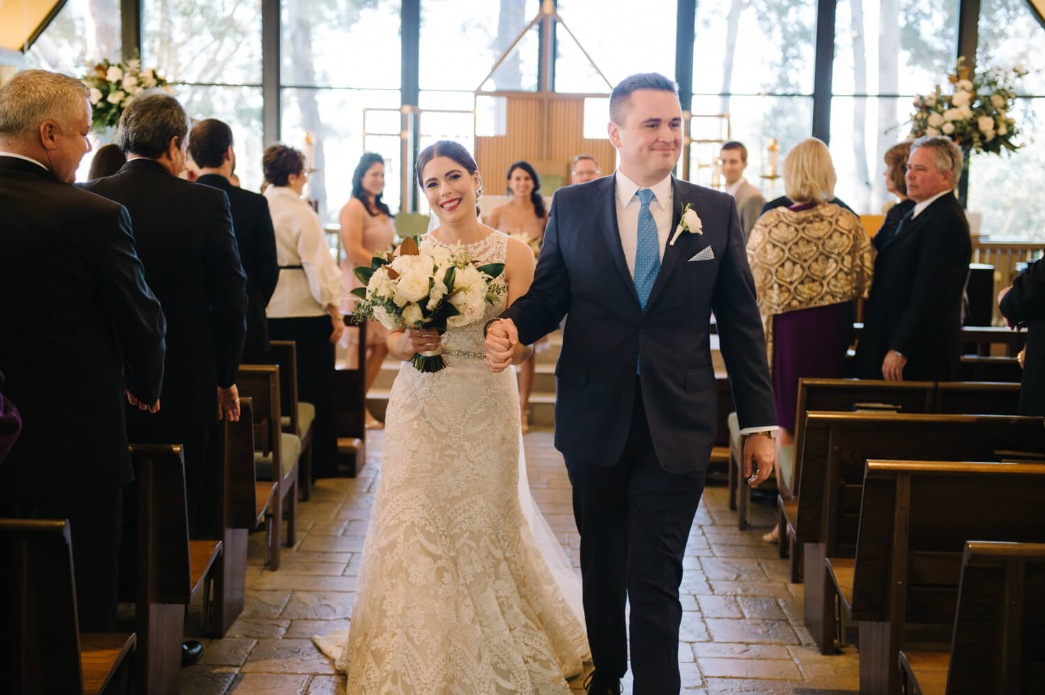 bride and groom walk down aisle after all hallows wedding ceremony