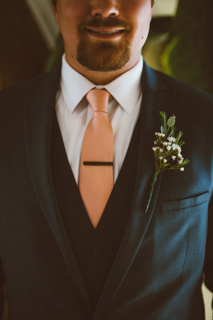 groom blue suit pink tie white boutonniere