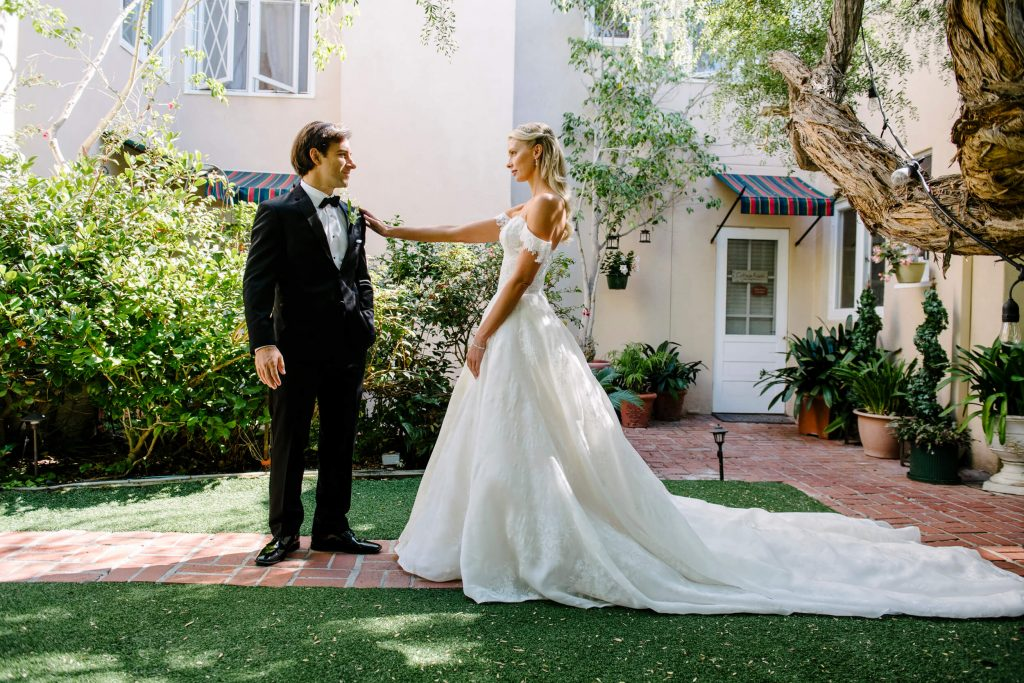 bride reaches out to groom as he turns around during first look in garden at la jolla bed breakfast inn