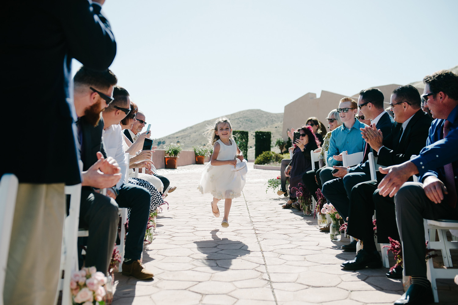 flower girl runs aisle high desert estate wedding