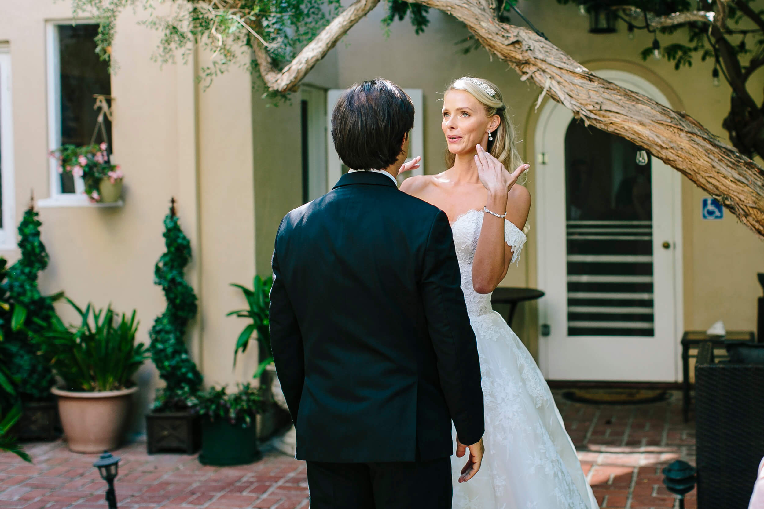 bride fans face with emotion during first look in garden at la jolla bed breakfast inn