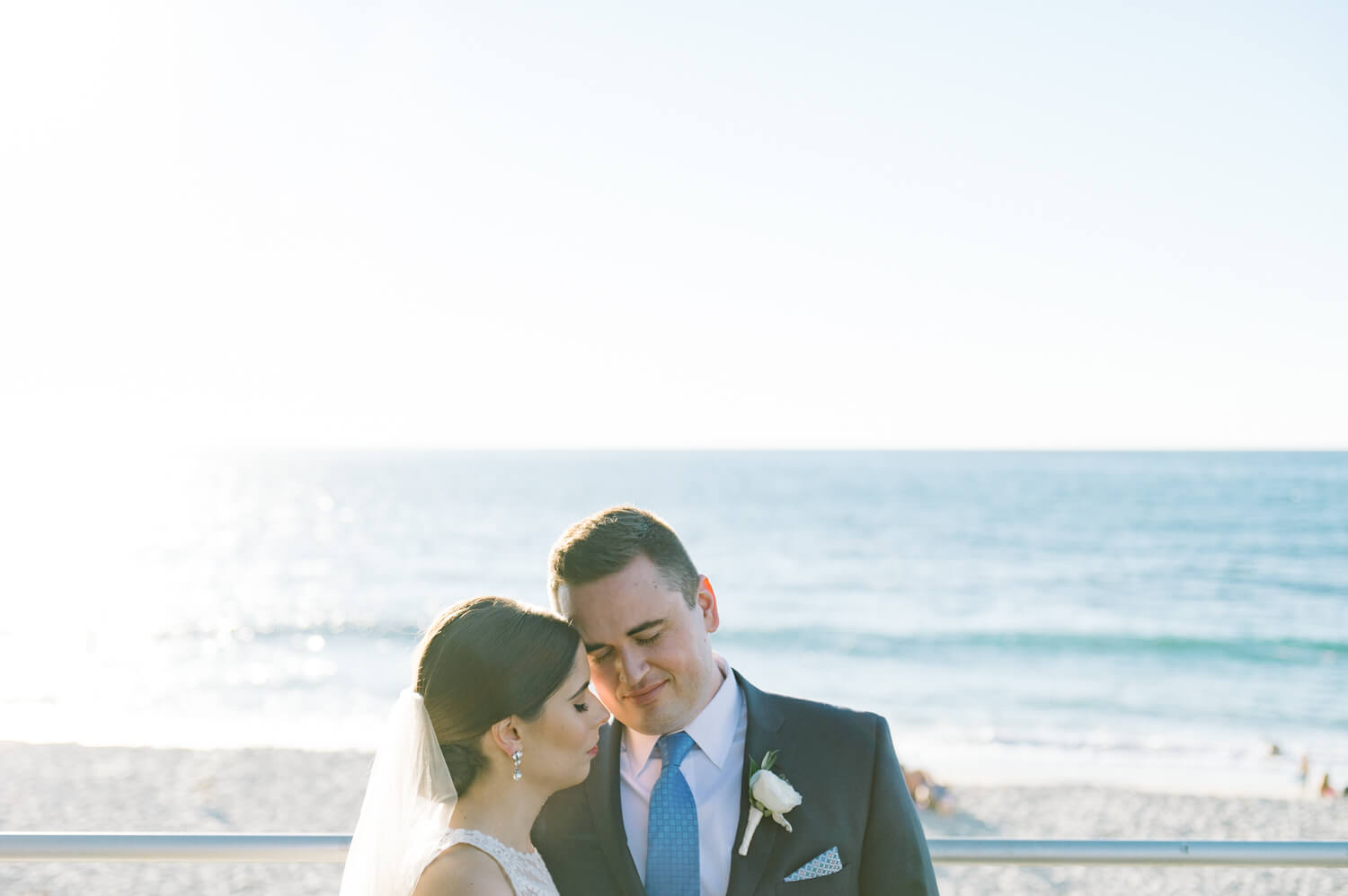 bride and groom pose for photo on la jolla beach after all hallows wedding
