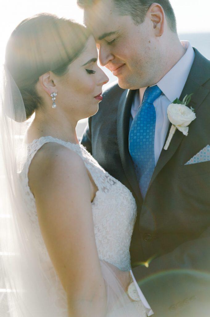 bride groom cuddle eyes close beach sunflare