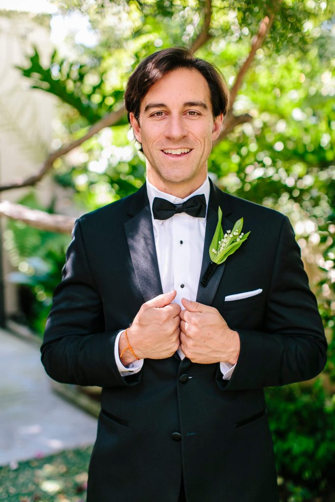 groom in tuxedo with bowtie and lily of the valley boutonniere