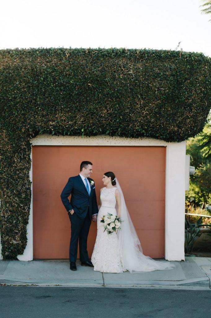 bride groom pose orange garage door green hedge