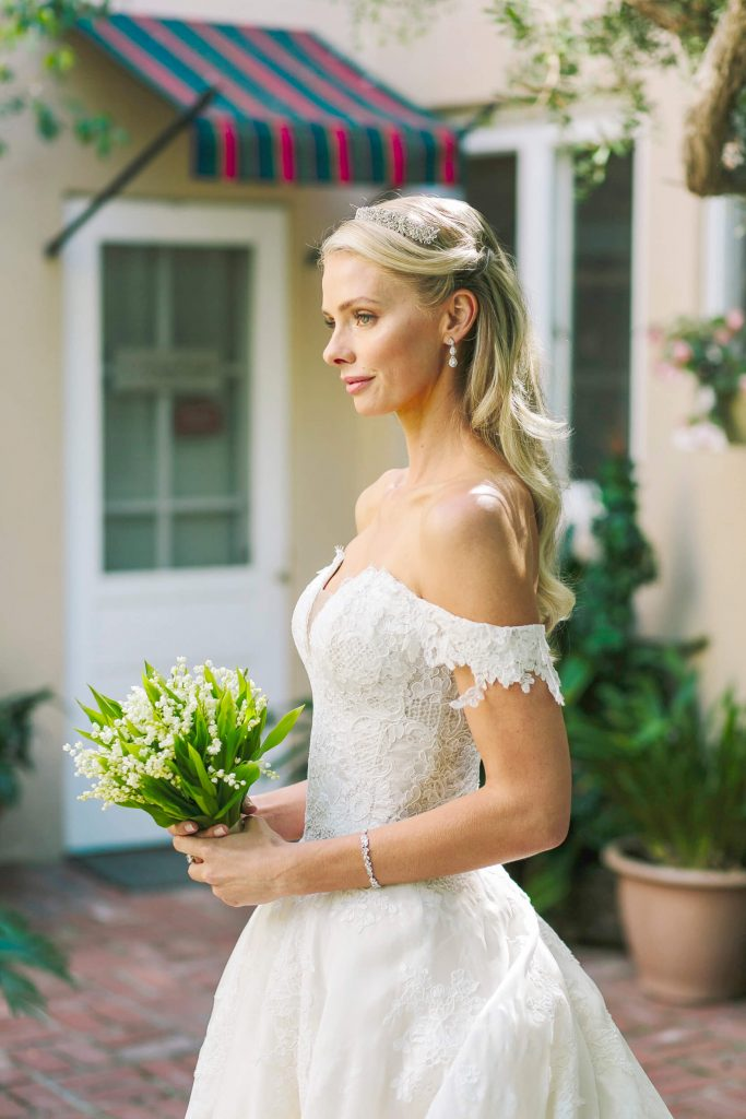 bride in monique lhuillier gown and lily of valley bouquet in garden at la jolla bed breakfast inn