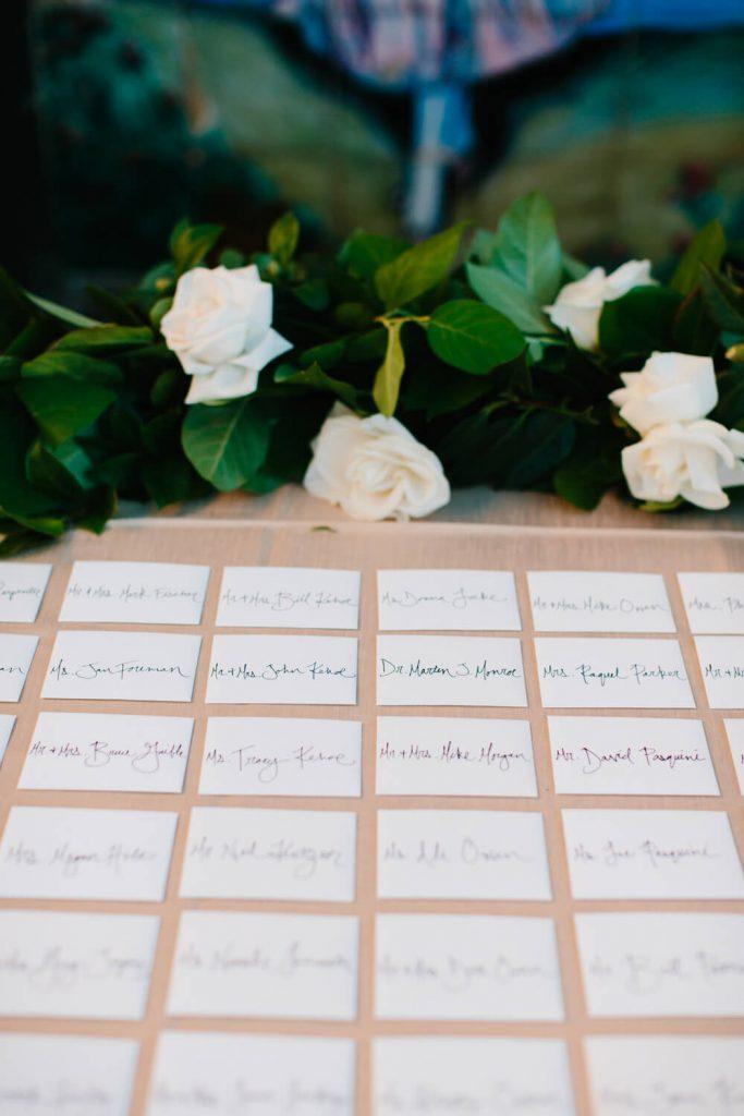 handwritten escort cards white camelias table