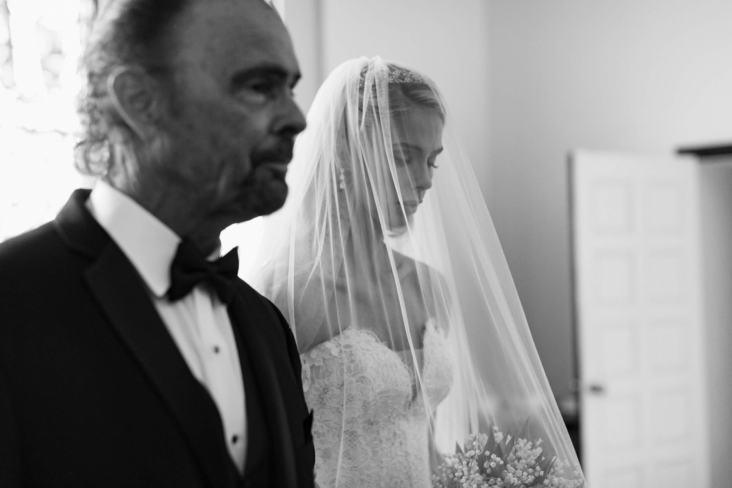 bride and father wait outside church before  royal family inspired wedding