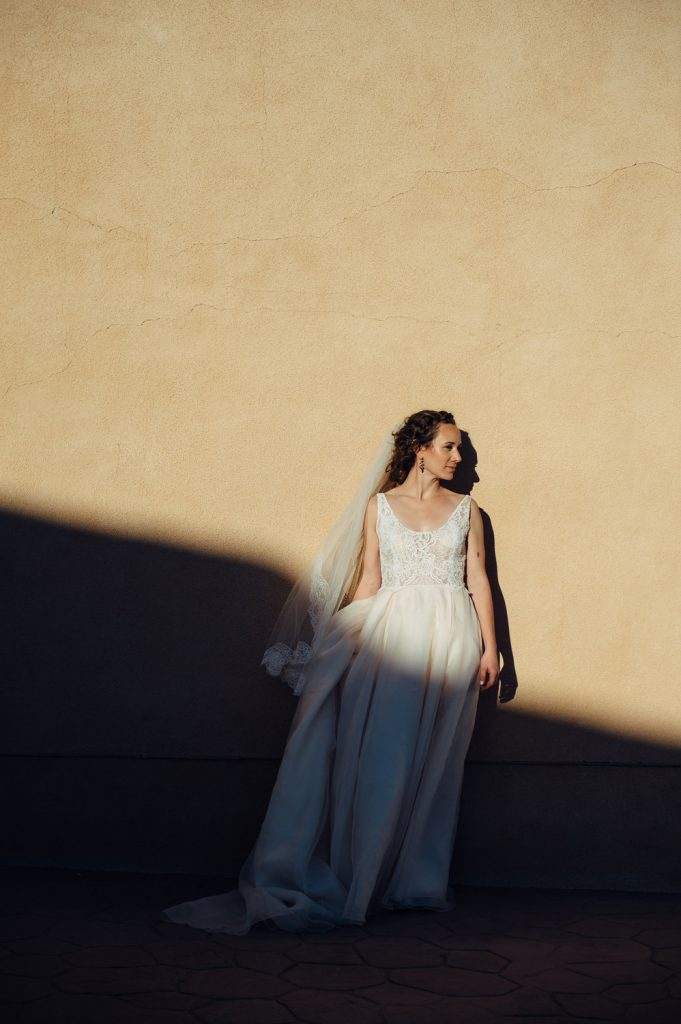 bride poses tan wall shadow