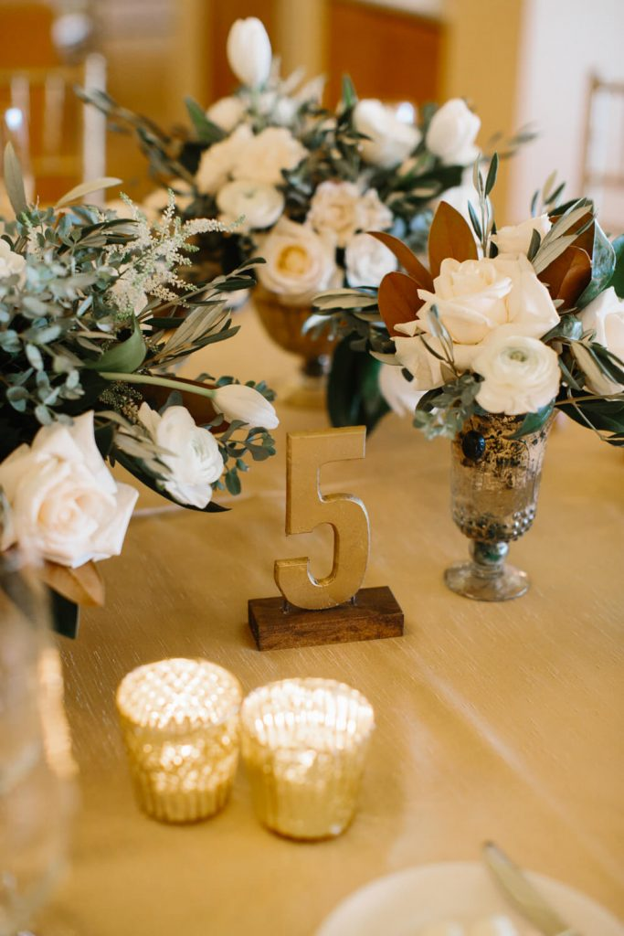 gold table number camelia mini roses olive branches centerpieces