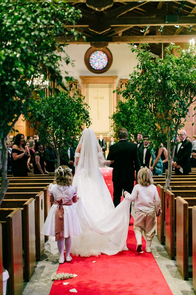 children hold wedding gown train for bride during processional