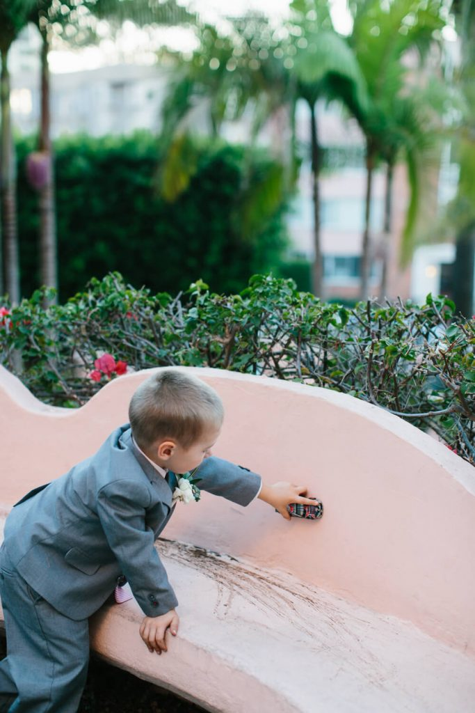 ringbearer gray suit plays with car pink bench la valencia hotel