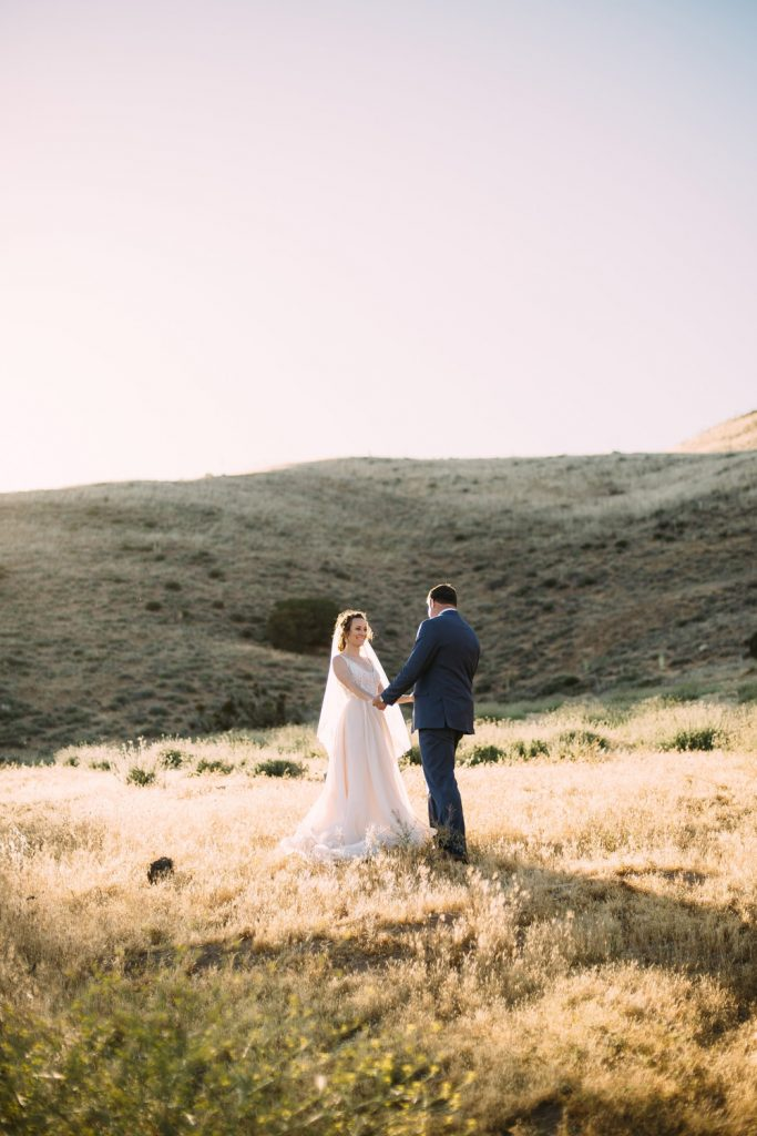 couple hold hands field summer high desert estate wedding