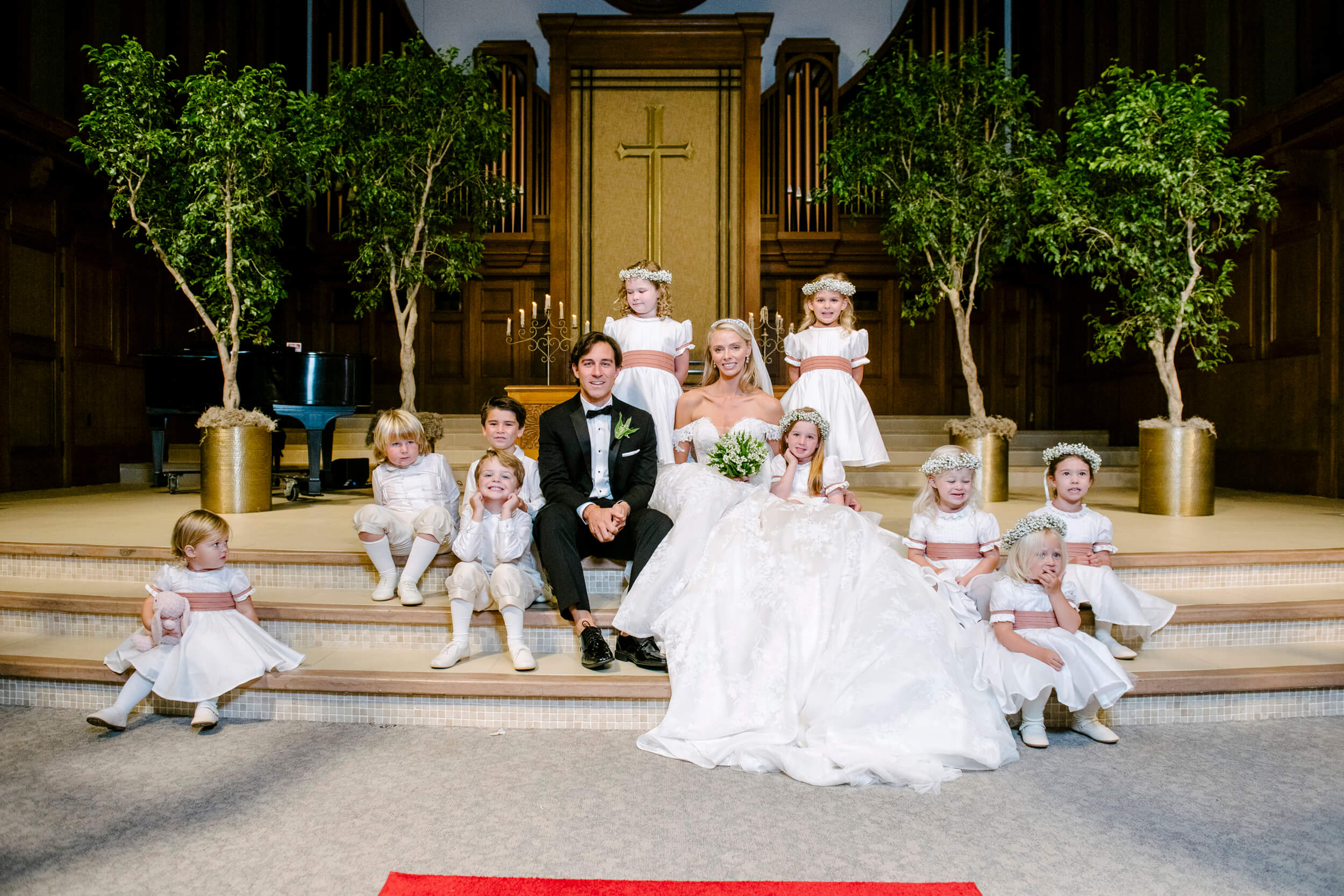 bride and groom pose with children in wedding party for royal family inspired wedding