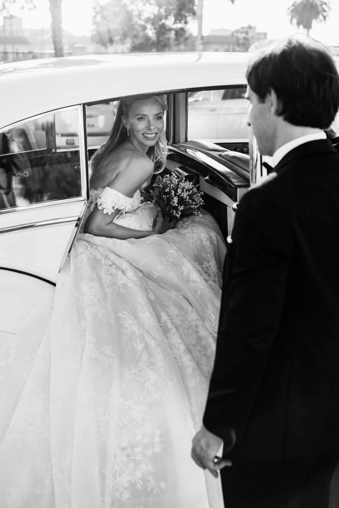 bride looks at groom from back seat of vintage rolls royce getaway car la jolla wedding ceremony