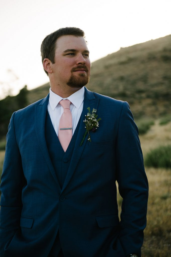 groom blue suit pink tie field high desert estate wedding