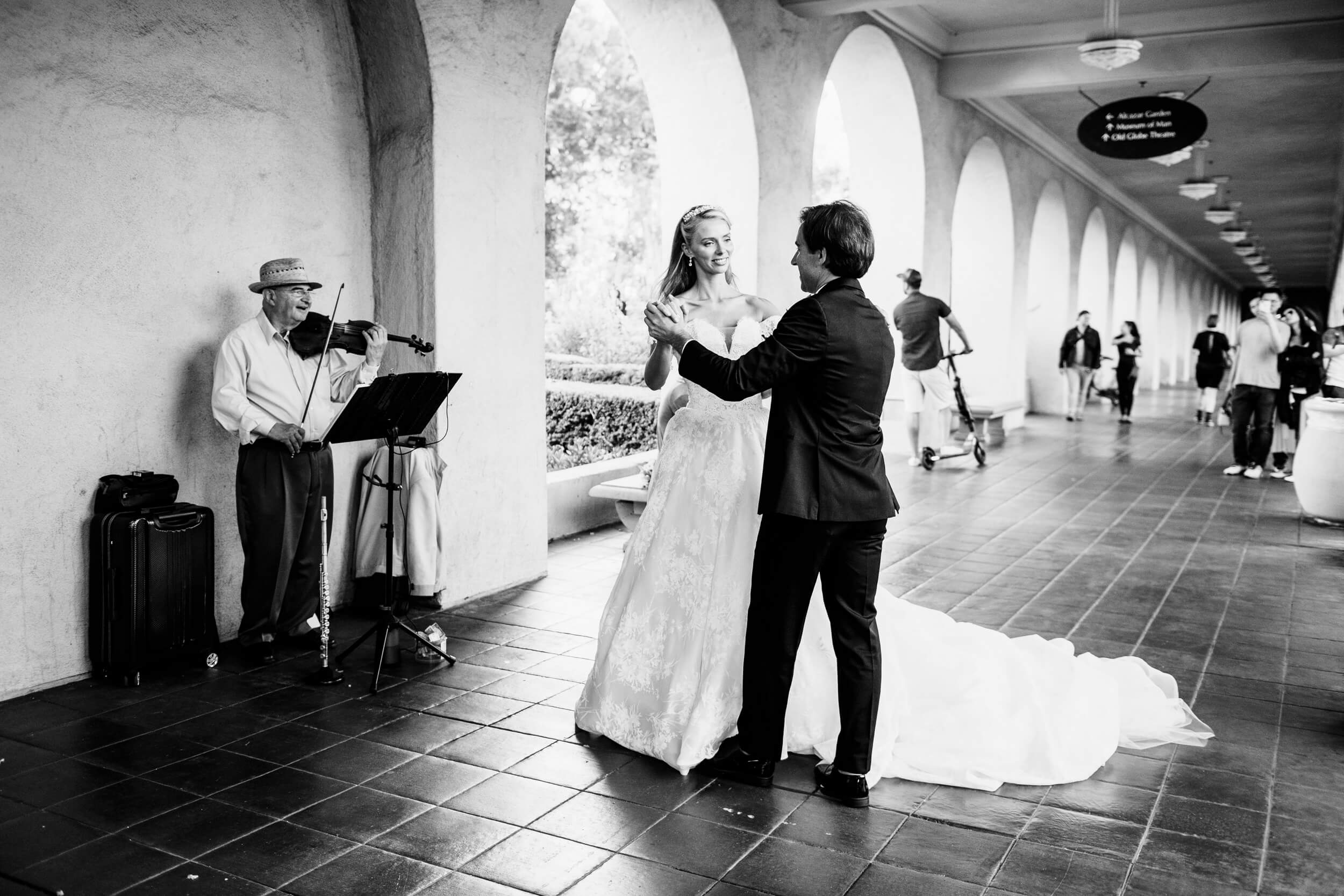 bride and groom dance while street musician performs balboa park