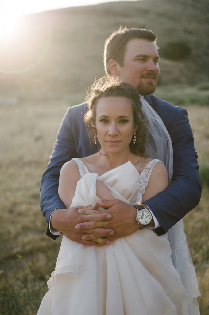 groom embraces bride holding gown high desert estate wedding