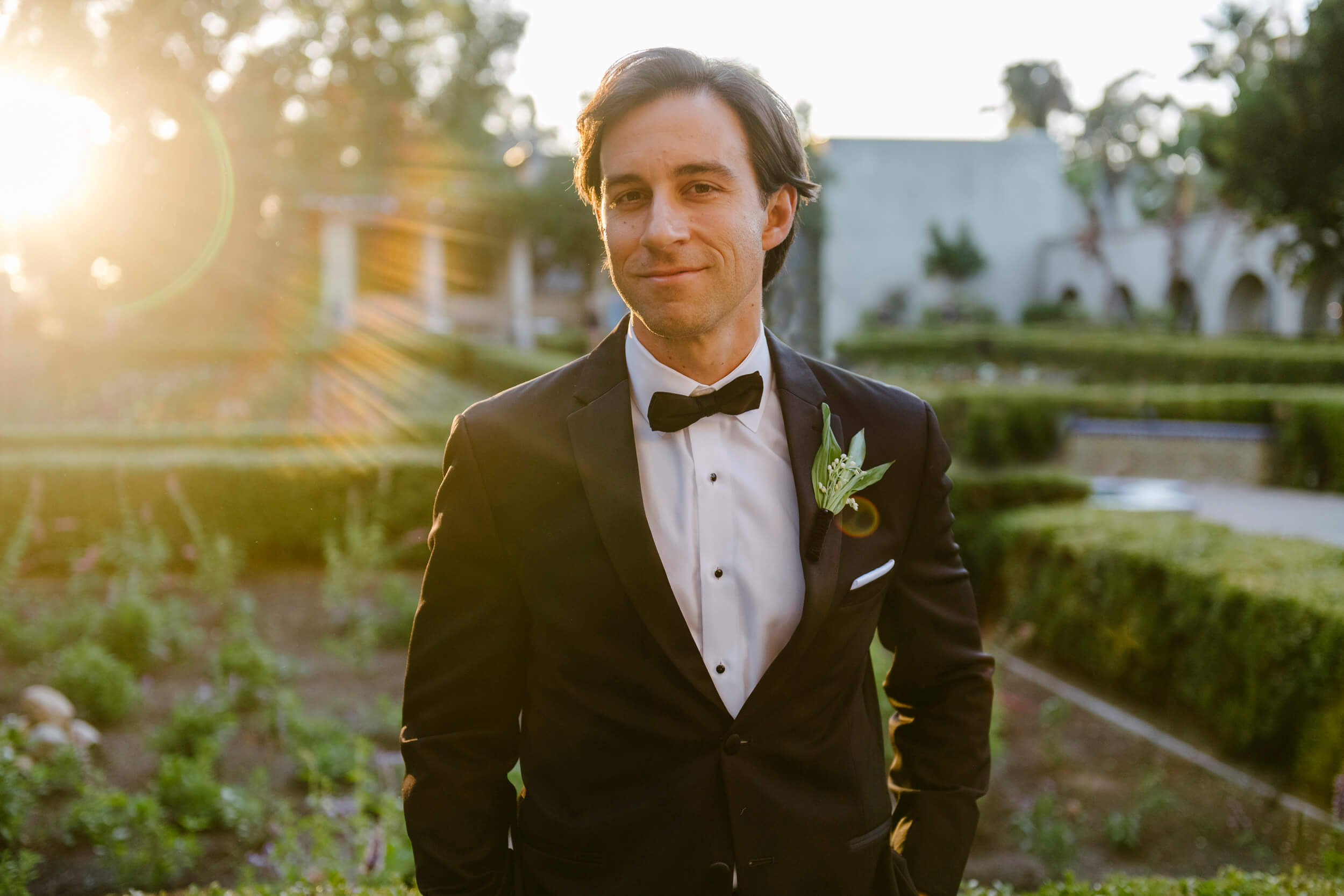 groom in tuxedo portrait at sunset in alcazar gardens