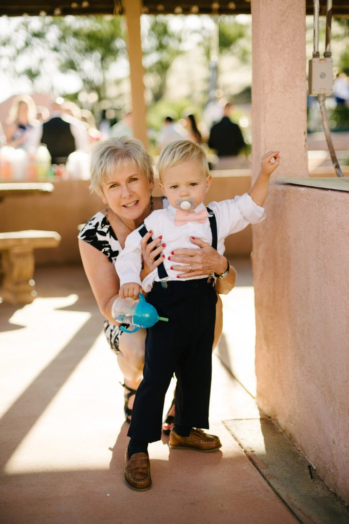 woman holds young ringbearer pink bowtie suspenders pacifier
