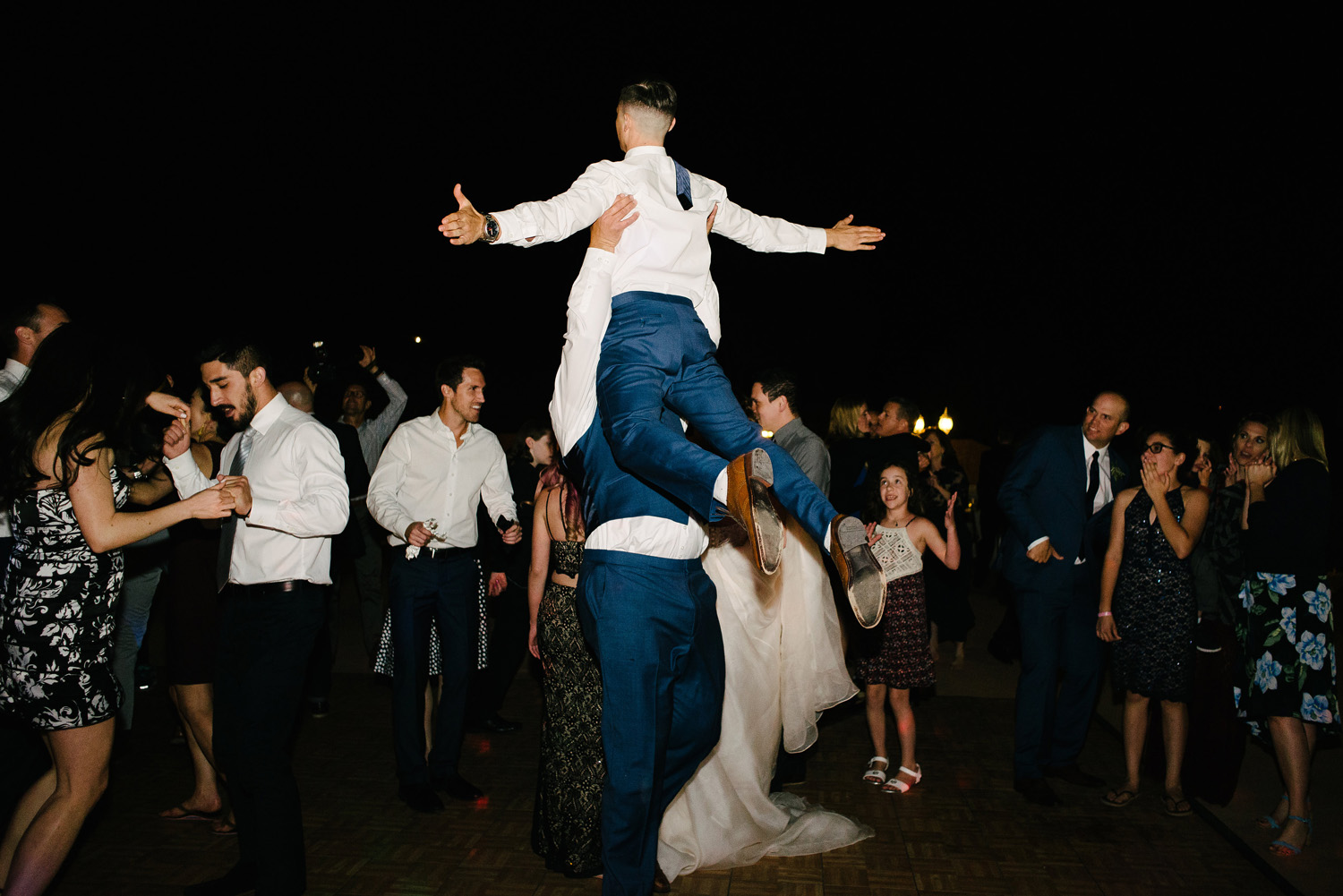 groom lifts groomsman dancing