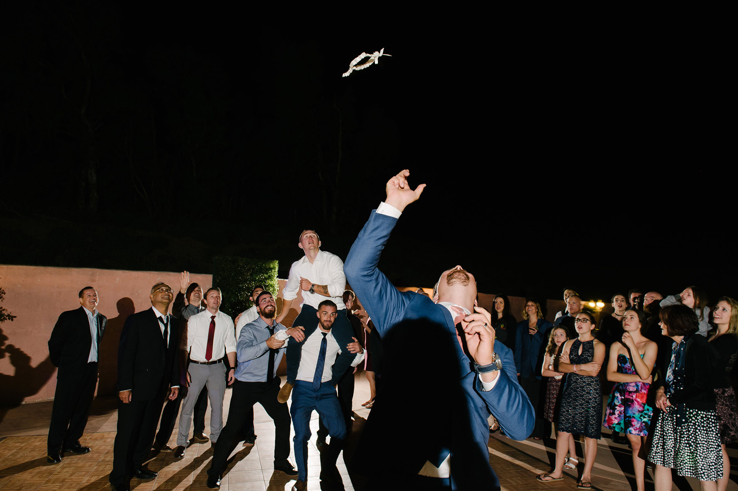 groom garter toss wedding guests on shoulders