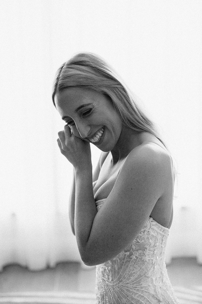 bride smiles as she puts on earrings before london west hollywood wedding