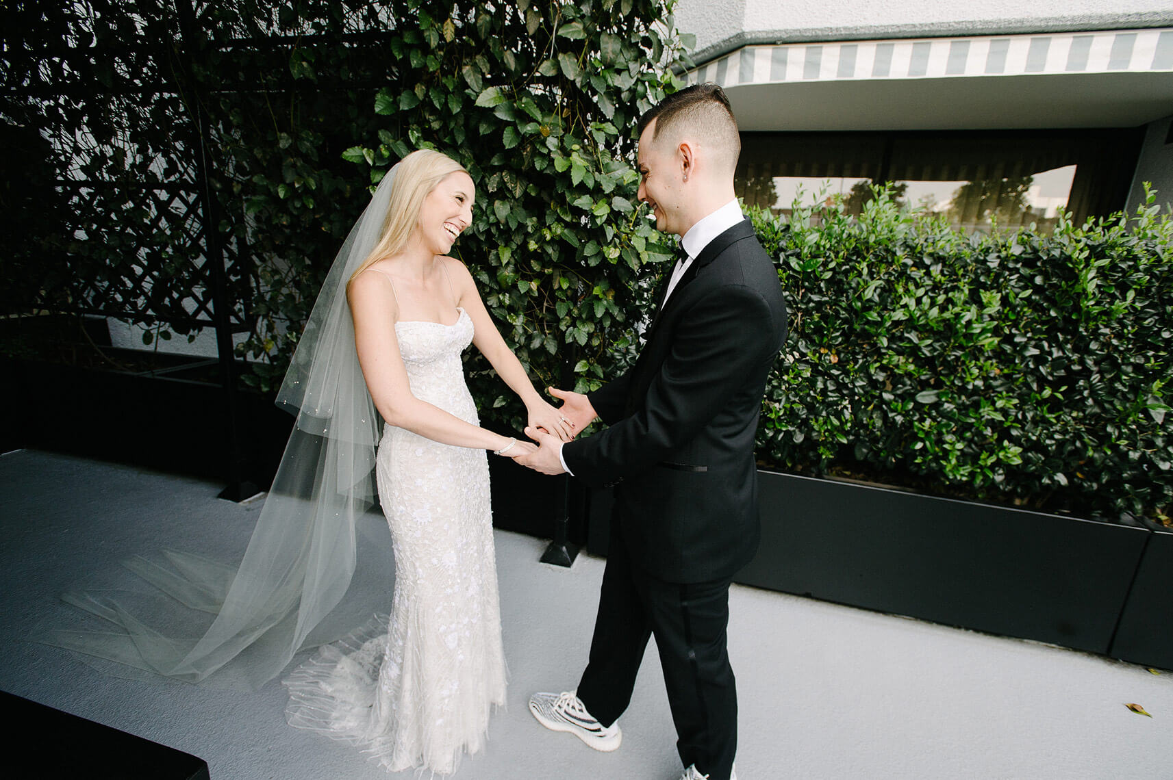 bride and groom smile as they see each other during first look at west hollywood wedding