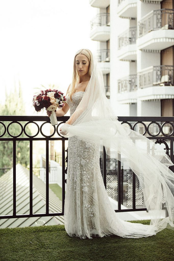 bride swings veil on balcony before london west hollywood wedding
