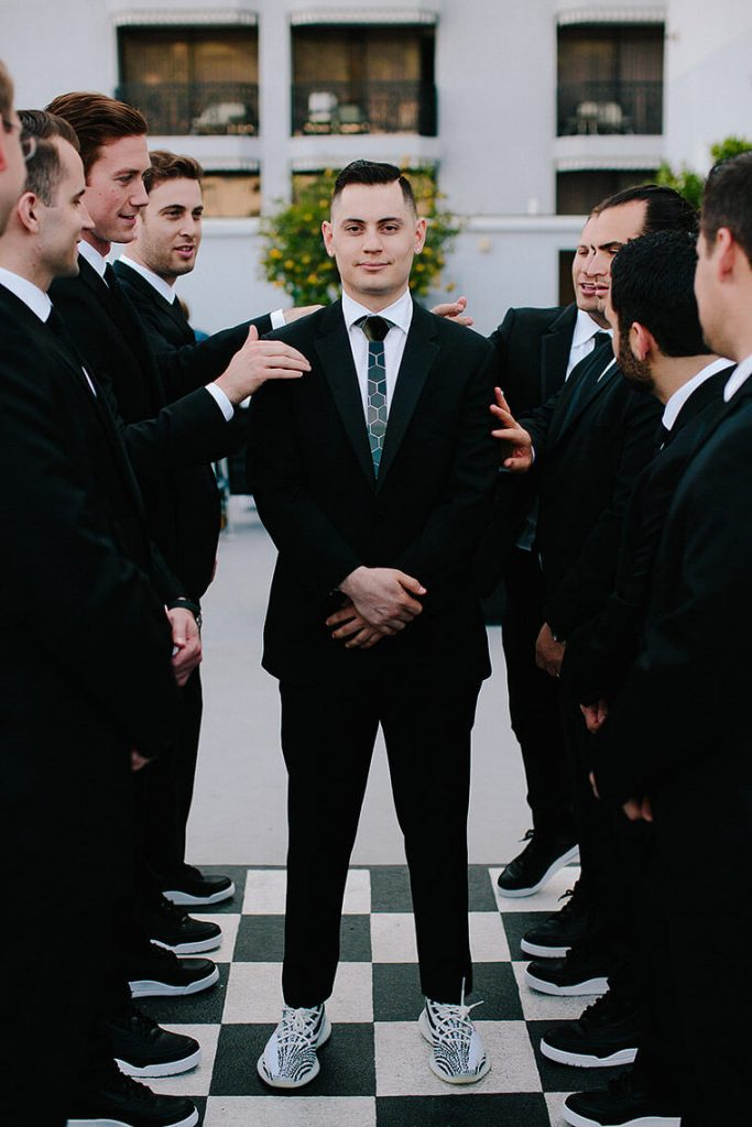 groom dressed in tuxedo with yeezy shoes standing on checkerboard with groomsmen before london west hollywood wedding