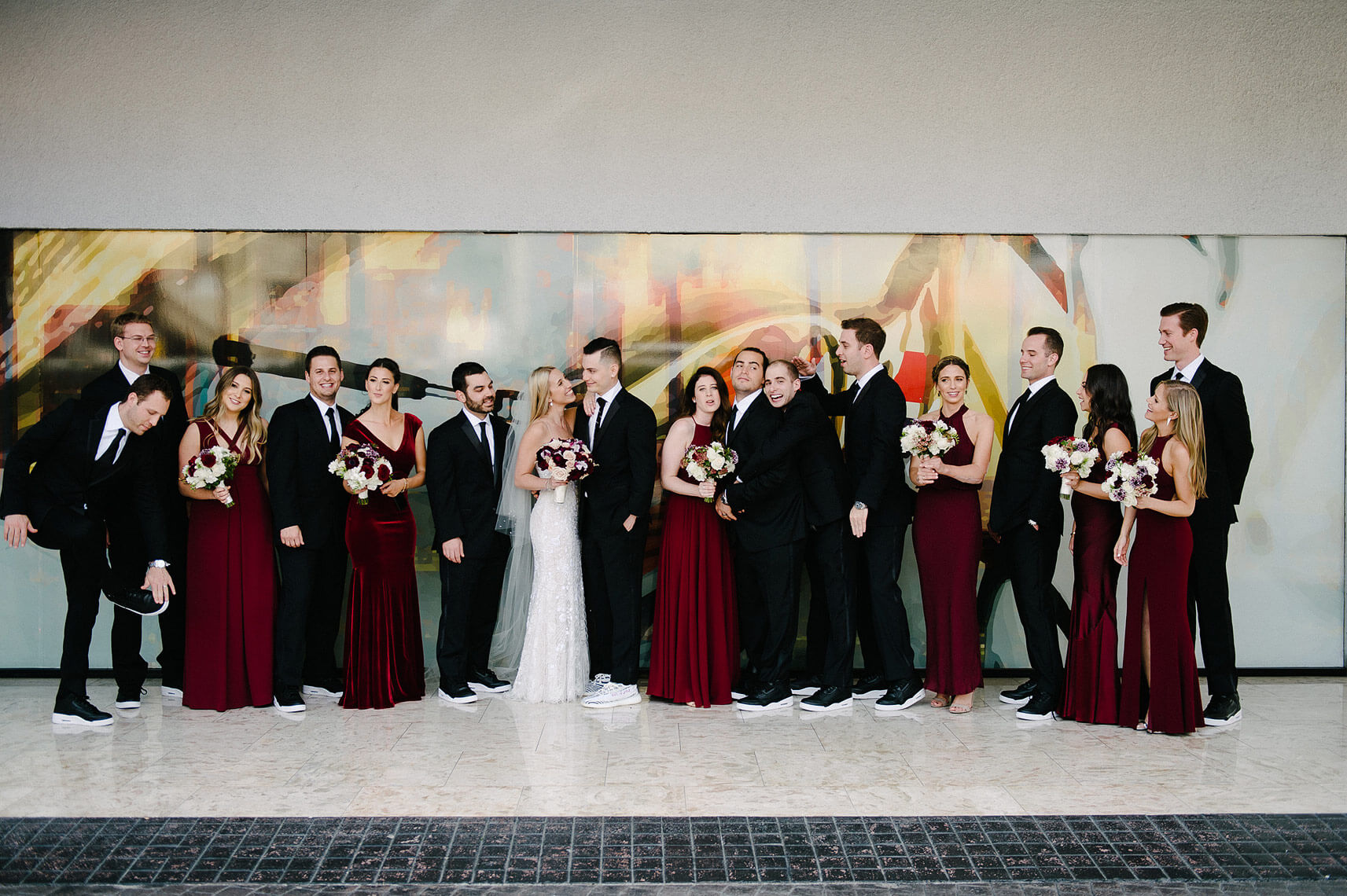 bridal party pose in front of large window art at west hollywood hotel wedding