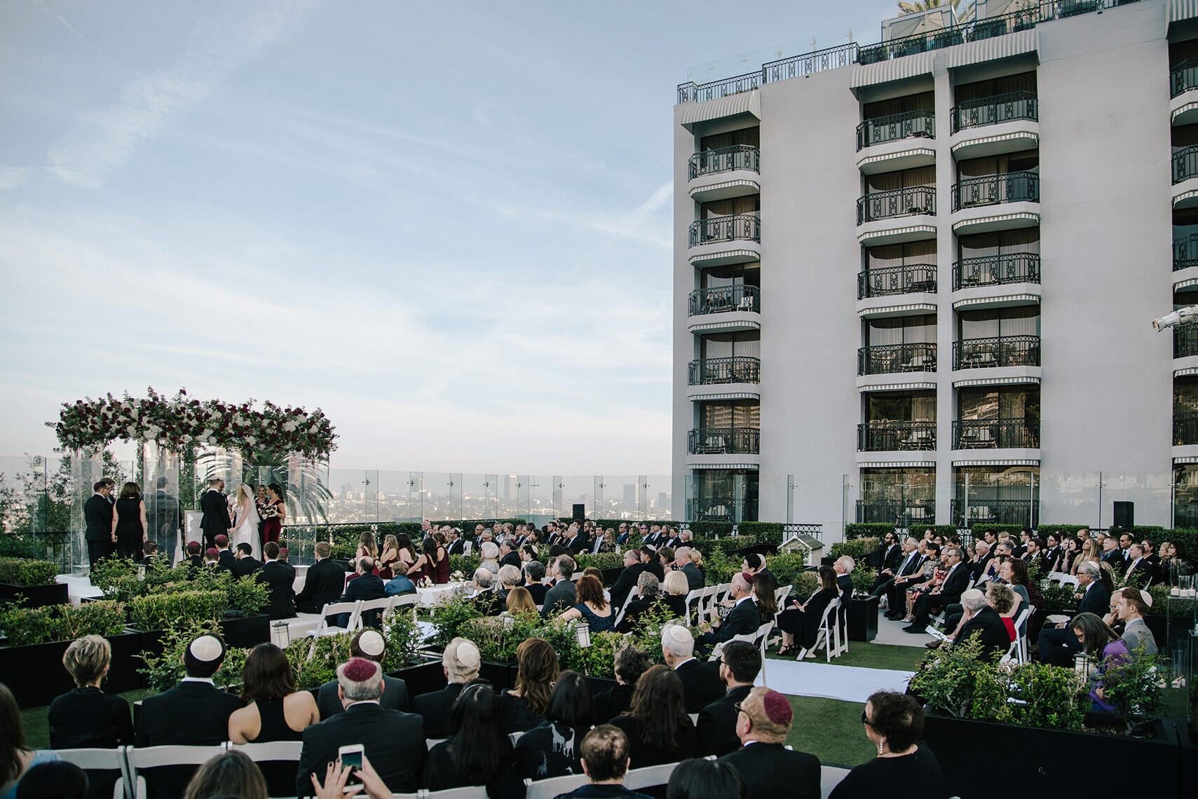 bride and groom and wedding guests during rooftop ceremony at london west hollywood
