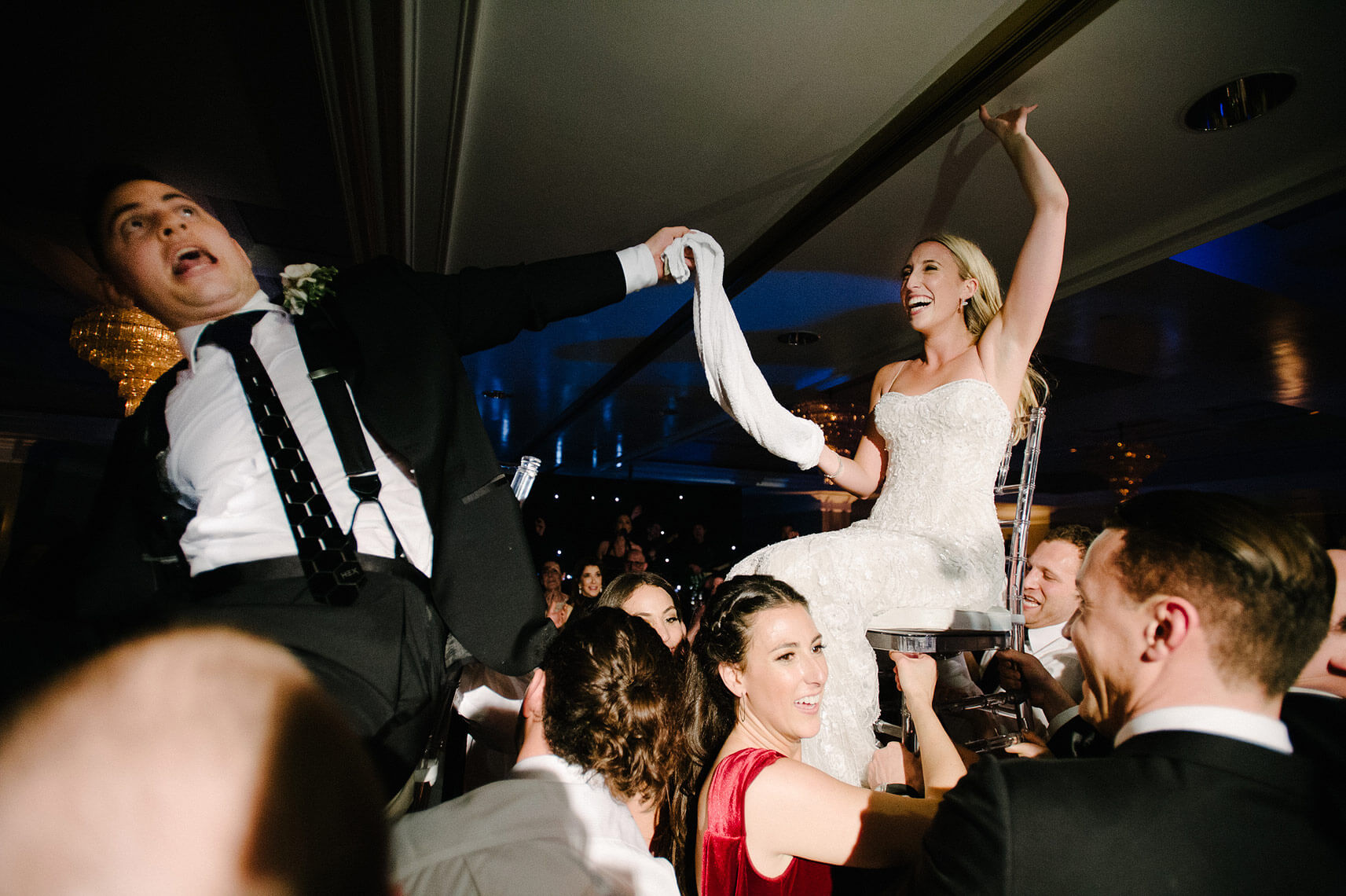 bride touches ceiling as groom ducks head during horah dance at west hollywood wedding reception