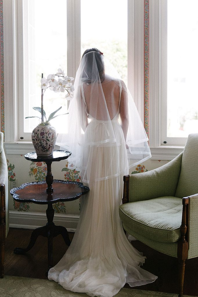 bride looks out window from darlington house bridal suite la jolla wedding