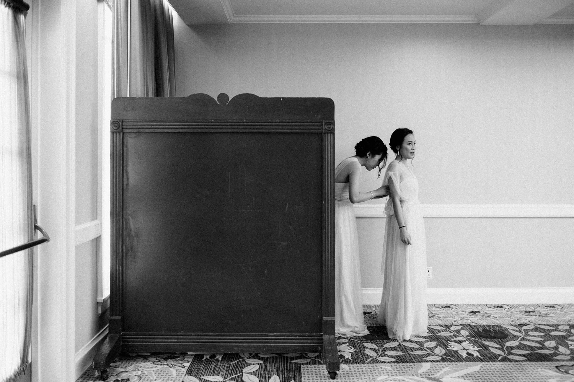 bridesmaids get dressed behind rolling wooden wall