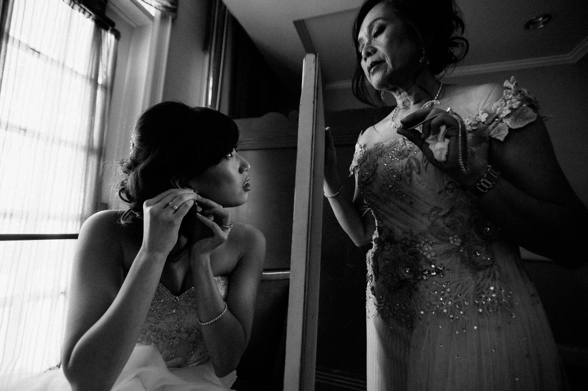 bridesmaid puts on earrings while mother holds mirror